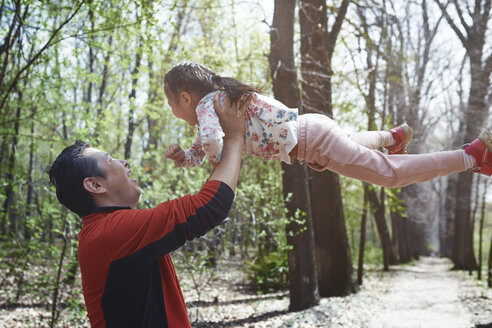 Father and daughter having fun in a park - AZF00027