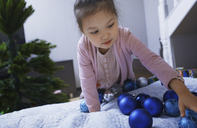 Portrait of little girl with blue Christmas baubles at home - AZF00036