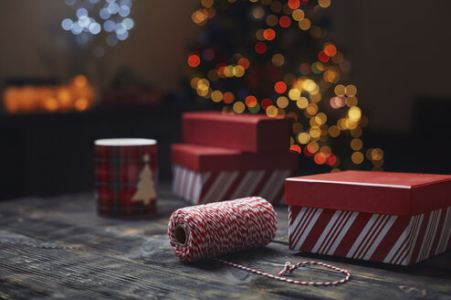Roll of red-white packthread and gift boxes in front of lighted Christmas tree - AZF00045