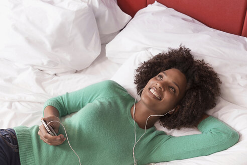 Woman listening to earphones on bed - ISF17201