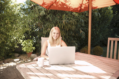 Young woman using laptop in garden - KMKF00401