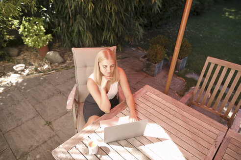 Young woman using laptop in garden - KMKF00404