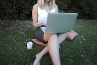 Young woman sitting on cushion on meadow, using laptop - KMKF00410