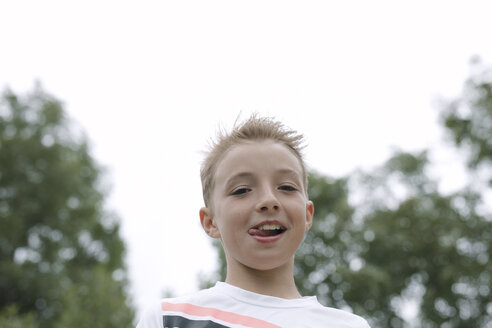 Portrait of blond boy sticking out tongue - KMKF00419