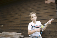 Portrait of blond boy with tennis racket and ball - KMKF00422