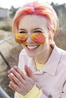 Portrait of young laughing woman, sun glasses and pink jeans jacket - AFVF01028