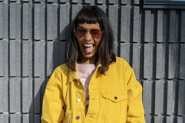 Portrait of young woman, wearing yellow jeans jacket - AFVF01034