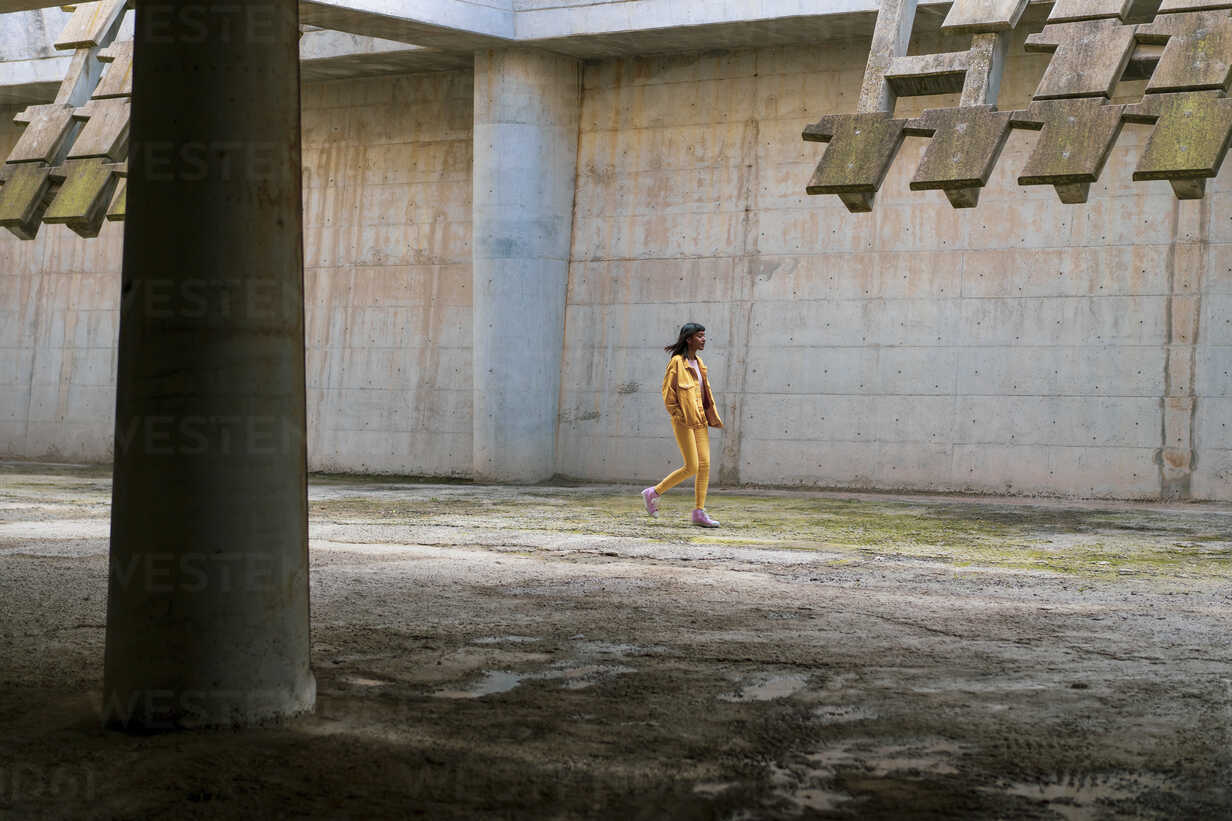 Young woman wearing yellow jeans clothes, walking - AFVF01040 - VITTA GALLERY/Westend61
