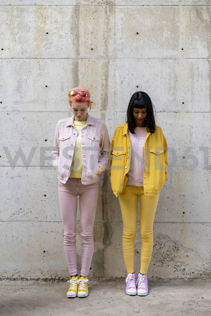 Two alternative friends having fun, wearing yellow and pink jeans clothes, looking down - AFVF01043