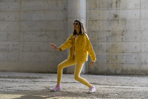 Woman wearing yellow jeans clothes, dancing - AFVF01046