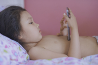 Little girl lying on bed playing with smartphone - AZF00060