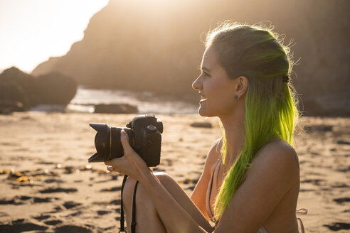 USA, California, West Coast, young woman with dyed green hair and camera sitting on the beach - AFVF01058