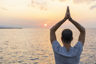 Spain. Man doing yoga during sunrise, raising arms, rear view - AFVF01061