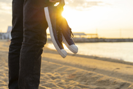 Spain. Man holding shoes, at a beach during sunrise - AFVF01070