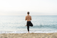 Spain. Man doing yoga on the beach in the evening, tree position, rear view - AFVF01073