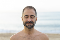 Portrait of happy man on a beach in the evening - AFVF01076