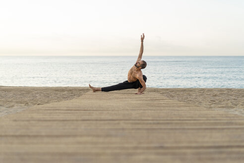 Spain. Man doing yoga on the beach in the evening - AFVF01079