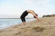 Spain. Man doing yoga on the beach in the evening, upward bow - AFVF01082