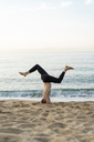 Spain. Man doing yoga on the beach in the evening - AFVF01085