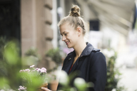 Smiling young woman choosing potted plant in front of a flower shop - SGF02198