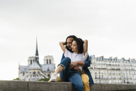 France, Paris, young couple sitting on wall at river Seine - AFVF01092
