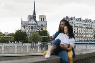 France, Paris, couple sitting on wall at river Seine in front of Notre Dame - AFVF01095