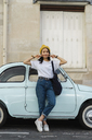 Portrait of young woman standing at small car - AFVF01101