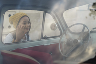 Young woman looking into small vintage car - AFVF01104