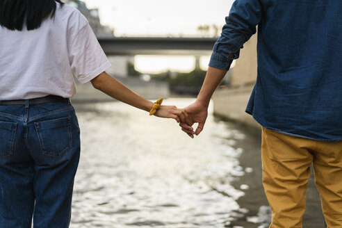 France, Paris, couple holding hands at river Seine - AFVF01107