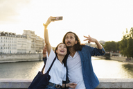 France, Paris, happy young couple taking a selfie at river Seine at sunset - AFVF01119