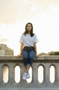 France, Paris, portrait of young woman sitting on railing at river Seine at sunset - AFVF01125