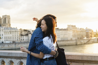 France, Paris, happy young couple hugging at river Seine at sunset - AFVF01128