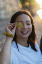 Portrait of happy young woman holding leaf in front of her eye - AFVF01140