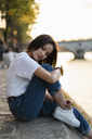 France, Paris, portrait of young woman at river Seine at sunset - AFVF01143