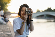 France, Paris, portrait of young woman with camera at river Seine at sunset - AFVF01146