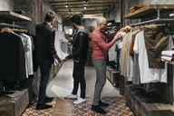 Three men in modern menswear shop with new collection - JRFF01701