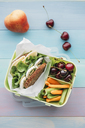 Healthy school food in a lunch box, vegetarian sandwich with cheese, lettuce, cucumber, egg and cress, sliced carrot and celery, cherries and pear - IPF00466
