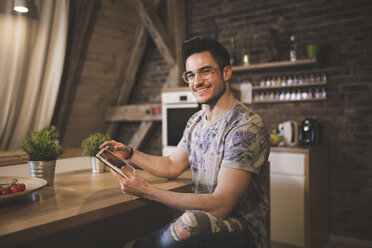 Portrait of smiling young man using tablet in kitchen at home - AWF00125