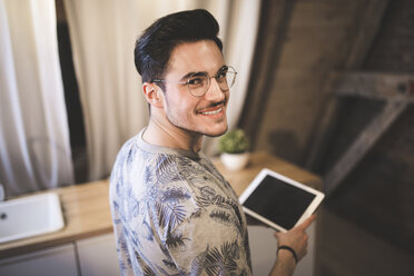 Portrait of smiling young man using tablet at home - AWF00128