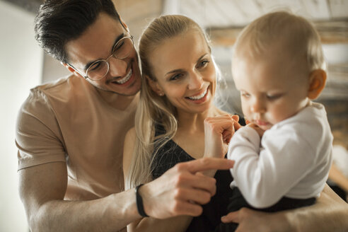 Happy young parents spending time at home with their baby girl - AWF00143
