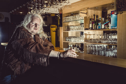 Portrait of blond rocker wearing brown leather jacket standing at counter of an old-fashioned pub - FRF00701