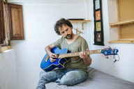 Spain, Man playing bass guitar in his room - KIJF01972