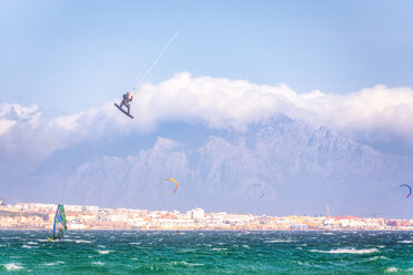 Spain, Andalucia, Tarifa, windsurfers and kite surfers on the sea with mountains of Morocco in the background - SMAF01088