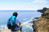 Spain, Canary Islands, Gran Canaria, Man with backpack sitting on cliff - KIJF01975
