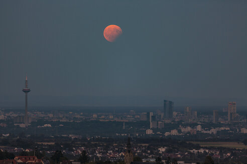Germany, Hesse, Hochtaunuskreis, Full moon with partial eclipse rising above the city of Frankfurt - THGF00057