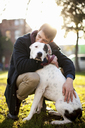 Man hugging dog in park - ISF17899