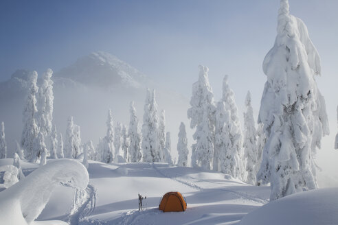 A bright orange tent sits on a snowy ridge overlooking a mountain in the distance. - MINF02935