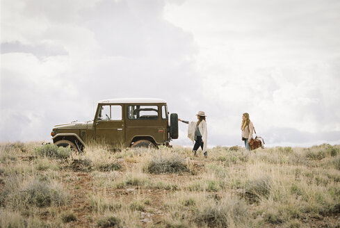 Two women by a jeep in open space, loading up for a road trip. - MINF02971