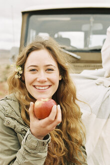 A young woman holding out a red skinned apple. - MINF02974