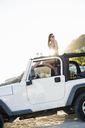 Woman sitting on roof of jeep on beach - ISF17979